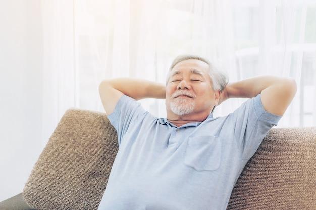 Un vecchio in pensione sorridente, uomo anziano che si rilassa sul divano nel soggiorno di casa sua - concetto di felicità senior di stile di vita