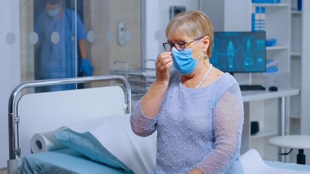 Donna anziana in pensione che indossa una maschera all'appuntamento medico durante la crisi pandemica sanitaria globale covid-119. paziente anziano in attesa dei risultati nel moderno reparto privato. sistema medico sanitario per coronavirus