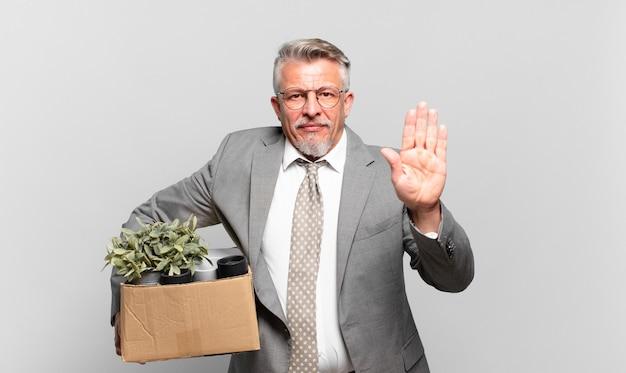 Uomo d'affari senior in pensione che sembra serio, severo, dispiaciuto e arrabbiato che mostra il palmo aperto che fa un gesto di arresto