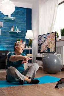 Donna anziana in pensione in abiti sportivi seduta su un tappetino da yoga che guarda una lezione di fitness sul portatile praticando esercizi per le braccia che dimagriscono il peso