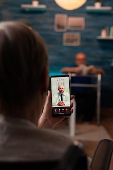 Donna in pensione che tiene smartphone con videochiamata per appuntamento medico e consultazione di telemedicina nel soggiorno di casa. vecchio con deambulatore seduto sul divano a leggere un libro