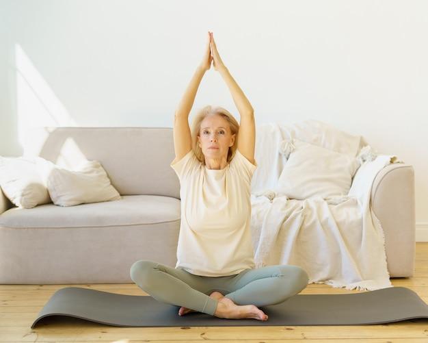 Donna in pensione nella posa del loto che pratica esercizi di yoga a casa seduta su mat