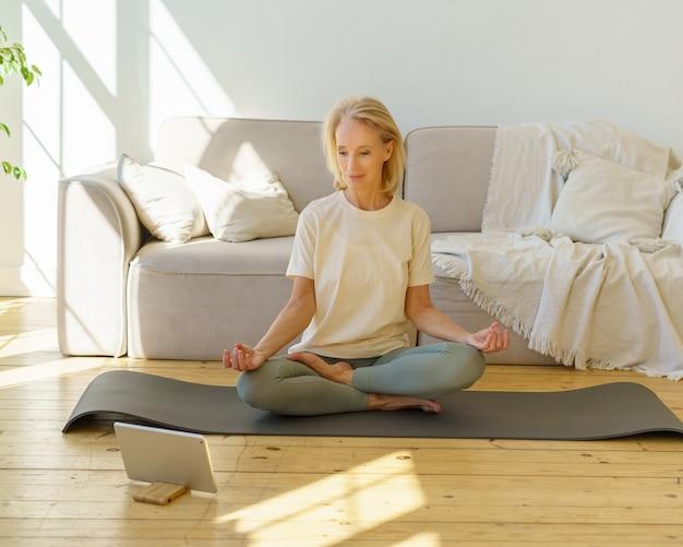 Donna in pensione che medita e pratica lo yoga mentre è seduta nella posa del loto sul pavimento a casa