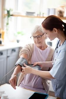 Infermiera di sorveglianza della donna pensionata che misura pressione sanguigna