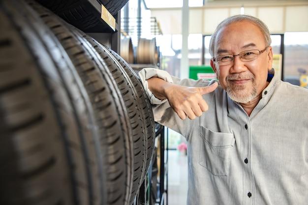 Uomo di pensionamento toccando e scegliendo per l'acquisto di un pneumatico in un supermercato. misurazione della ruota dell'auto in gomma.