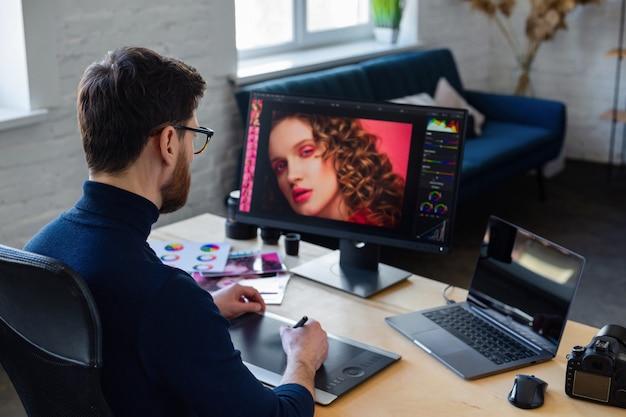 Ritocco di immagini in programma speciale. ritratto di grafico che lavora in ufficio con laptop, monitor, tavoletta grafica e tavolozza dei colori. posto di lavoro di ritoccatore in studio fotografico. agenzia creativa.