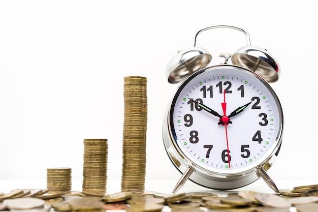 Retro sveglia e pila di monete
