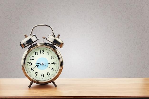 Retro sveglia sulla tavola di legno con il fondo porpora della parete