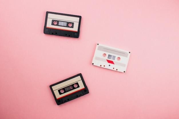Retro piatto audiocassetta giaceva su sfondo colorato blu rosa pastello. vista dall'alto con copia spazio. fashion design creativo in stile minimal anni '80 con duotoni.