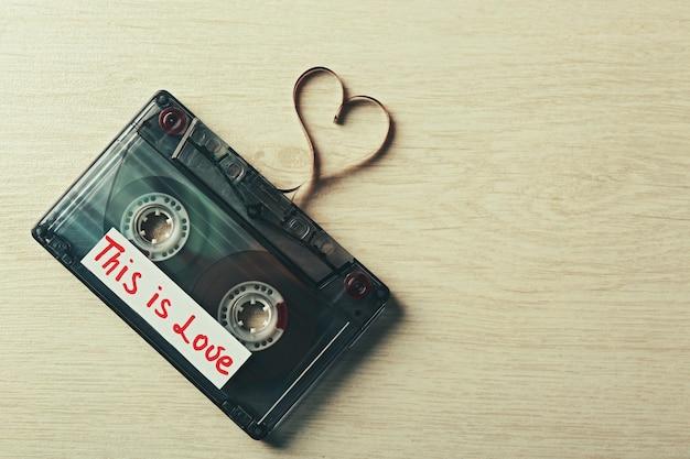 Cassetta audio retrò con nastro a forma di cuore su legno