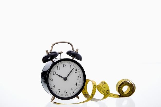 Retro sveglia nera con nastro di misurazione giallo su sfondo bianco concetto di successo