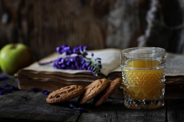 Libro retrò e bicchiere di succo d'arancia al mattino