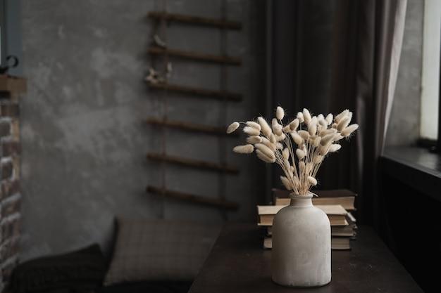 Bottiglia retrò con bouquet di erba coda di coniglio, libri sul tavolo marrone scuro.