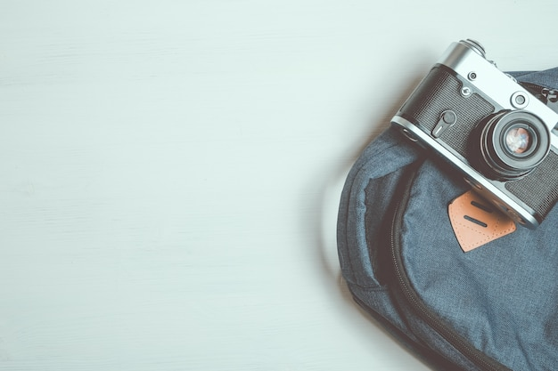 La retro macchina fotografica si trova su uno zaino alla moda su un fondo di legno bianco.