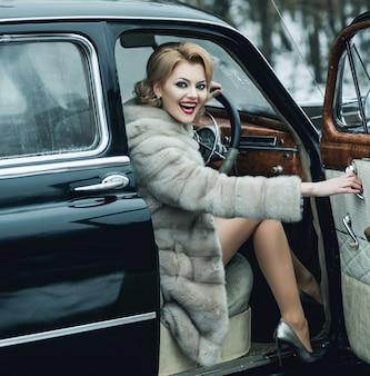 Retro automobile e donna sexy in cappotto di pelliccia. auto da collezione retrò e riparazione auto da autista.