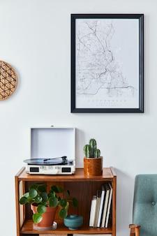 Composizione retrò dell'interno del soggiorno con mappa poster mock up, mensola in legno, libro, poltrona, pianta, cactus, registratore in vinile e accessori personali in un elegante arredamento per la casa