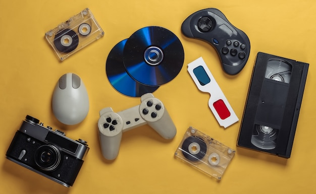 Intrattenimento retrò. attributi, gadget anni '80. tastiera, mouse per pc, compact disc, gamepad, occhiali anaglifi, audio e videocassetta, fotocamera su giallo