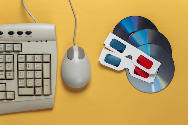 Intrattenimento retrò. tastiera antiquata, mouse per pc, compact disc, occhiali stereo anaglifi su un giallo