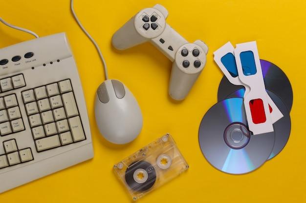 Intrattenimento retrò. tastiera antiquata, mouse per pc, compact disc, gamepad, occhiali anaglifi, audiocassetta su giallo