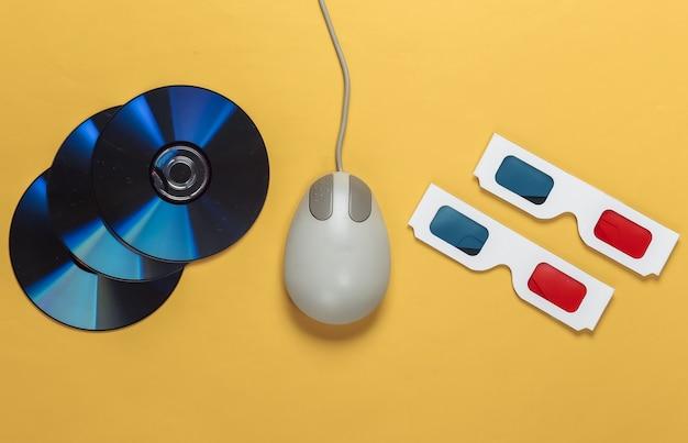 Intrattenimento retrò. mouse per pc vecchio stile, occhiali stereo anaglifi e cd su un giallo