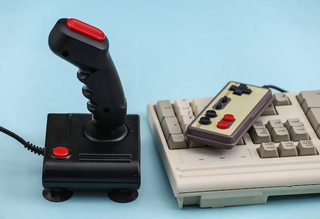 Gamepad retrò e joystick con tastiera pc su sfondo blu. videogioco, giochi anni '80.