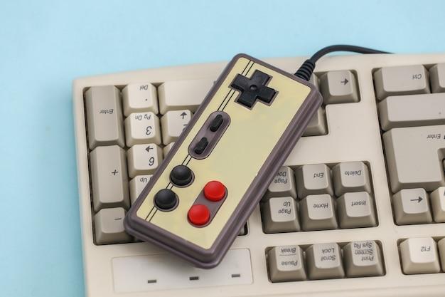 Gamepad retrò sulla vecchia tastiera del pc. sfondo blu. attributi anni '80, giochi