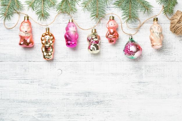 Ghirlanda retrò di decorazioni natalizie d'epoca e abete rosso su sfondo bianco copia spazio.