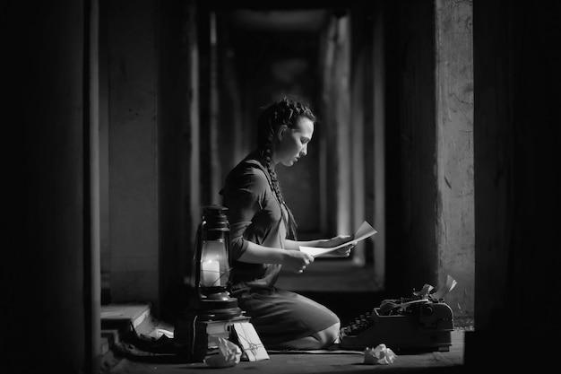 Ragazza retrò nella vecchia casa che legge libri e scrive una storia