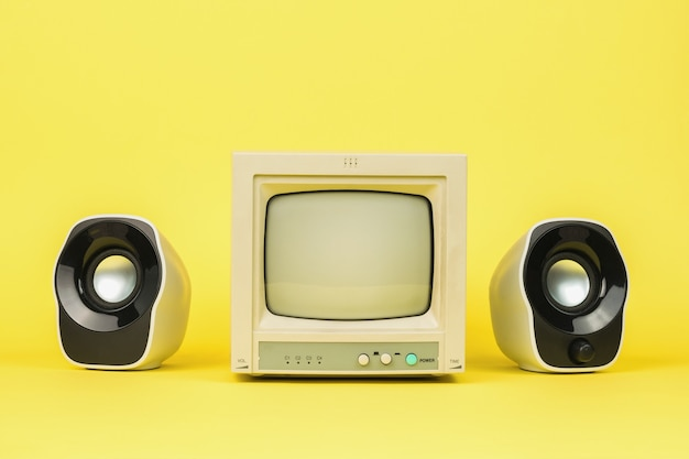 Monitor grigio retrò con altoparlanti su sfondo giallo. elegante attrezzatura vintage.