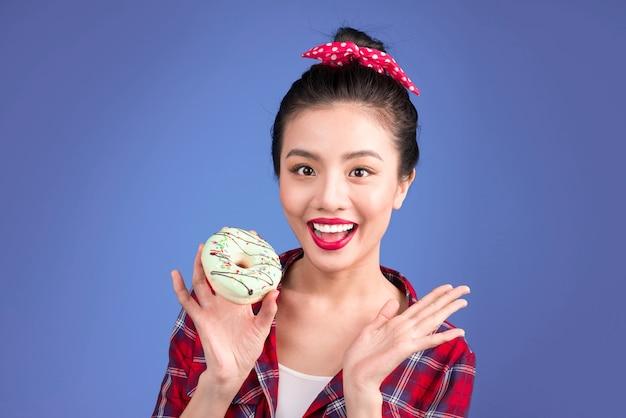 La donna allegra retrò gode di dolci, dessert in piedi su sfondo blu.