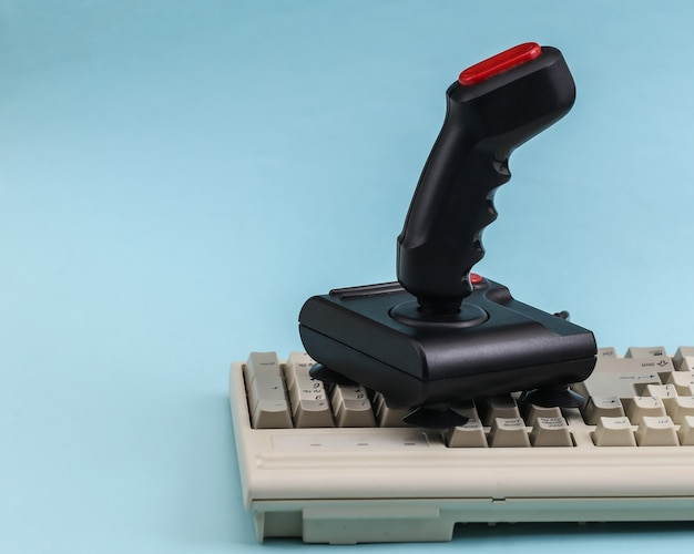 Joystick retrò sulla vecchia tastiera del pc. sfondo blu. attributi anni '80, giochi