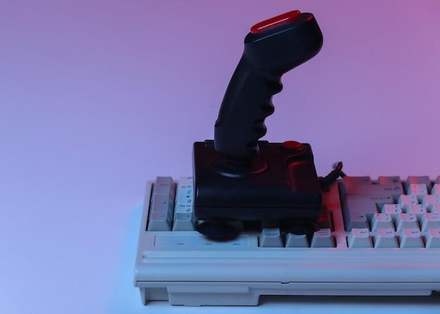 Joystick retrò sulla vecchia tastiera del pc. luce al neon sfumata rosso blu. attributi anni '80, giochi. onda retrò