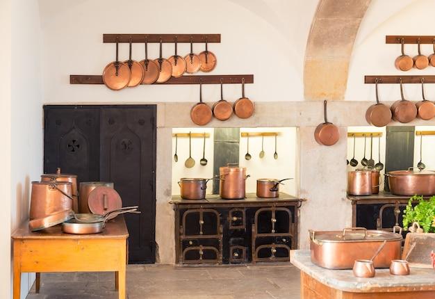 Interiore della cucina retrò con vecchie pentole e credenze in ottone