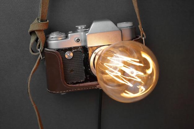 Lampada retrò da una vecchia macchina fotografica con una lampada edison su uno sfondo grigio