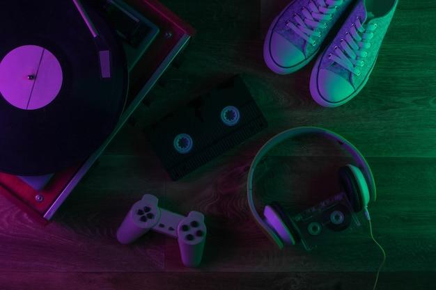 Media retrò e roba vecchio stile su un pavimento di legno con luce al neon verde e viola