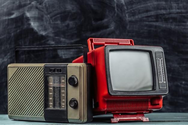 Media retrò. tv portatile vecchia scuola, ricevitore radio su sfondo lavagna