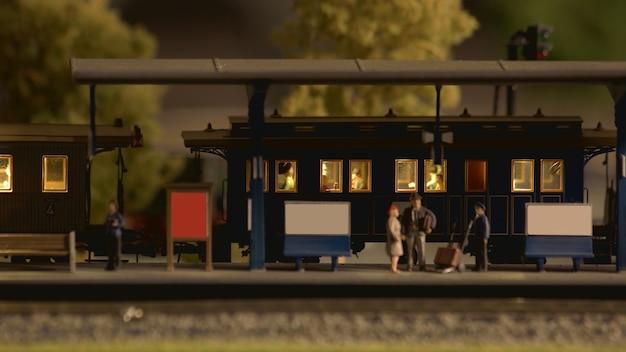Stazione ferroviaria in miniatura retrò con passeggeri.
