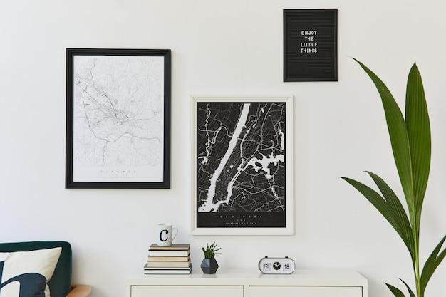 Composizione moderna retrò di interni del soggiorno con poltrona di design, due mappe poster mock up, orologio, pianta, decorazione, parete bianca e accessori personali. modello.
