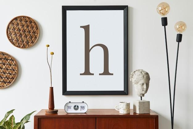 Composizione moderna retrò di interni del soggiorno con comò in teak di design, cornice nera per poster, orologio, fiori secchi, decorazione, parete bianca e accessori personali. modello.