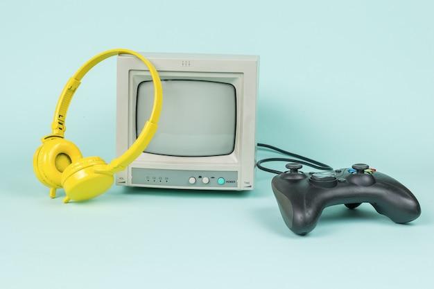 Monitor retrò, cuffie gialle e una console di gioco su sfondo blu. attrezzatura d'epoca.