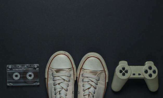 Retro vecchie scarpe da ginnastica, cassetta audio e gamepad su sfondo nero. anni 80. vista dall'alto