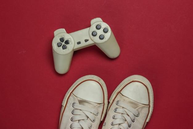 Retro vecchie scarpe da ginnastica e gamepad su sfondo rosso. anni 80. vista dall'alto
