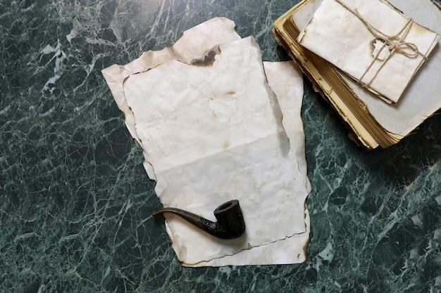 Carte retrò e libro sul tavolo da lavoro investigativo con sfondo di strumenti