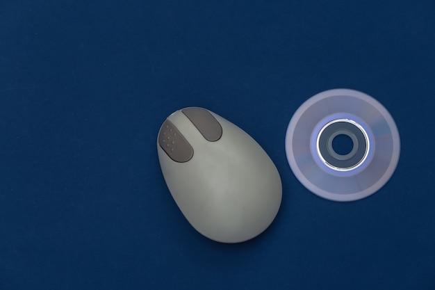 Mouse e cd retrò per pc su sfondo blu classico. colore 2020. vista dall'alto