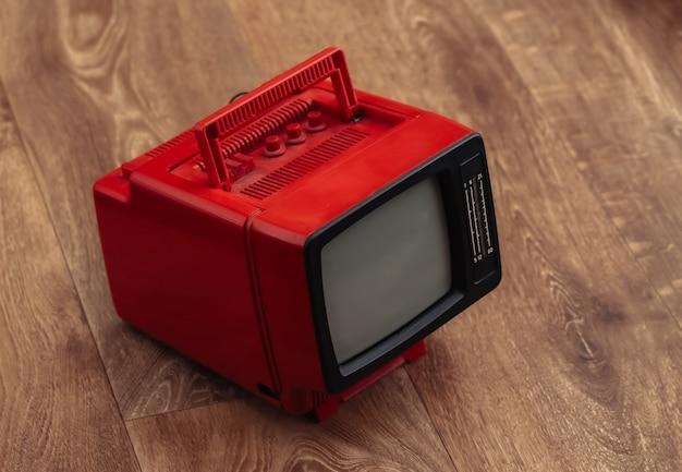 Mini tv rossa portatile retrò su pavimento in legno