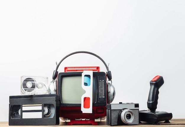 Mini televisore portatile retrò con cuffie, occhiali 3d, fotocamera, joystick, cassetta audio e video su sfondo bianco. attributi anni '80, stile retrò