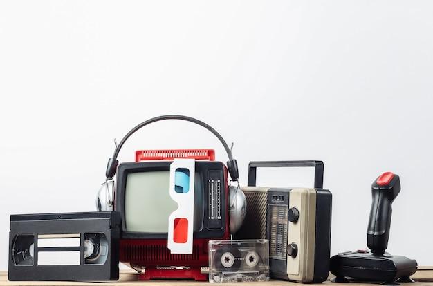 Mini televisore portatile retrò con cuffie, occhiali 3d, ricevitore radio, joystick, cassetta audio e video su sfondo bianco. attributi anni '80, stile retrò