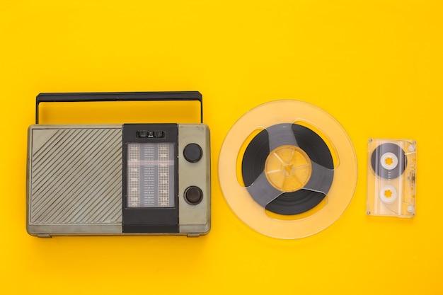 Ricevitore radio portatile retrò e bobina di nastro magnetico audio, cassetta audio su giallo