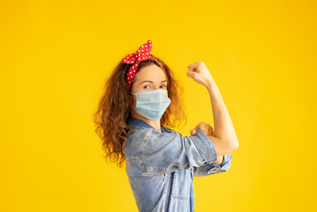 Retro ritratto di donna forte che indossa la maschera protettiva contro backgrond giallo