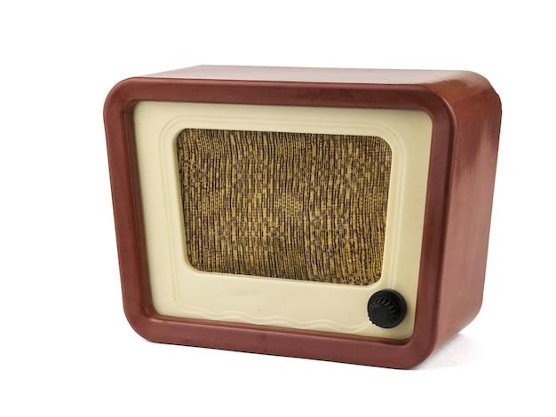 Radio retrò con manopola del volume nera isolata su superficie bianca. ingegneria radiofonica del passato. design retrò.